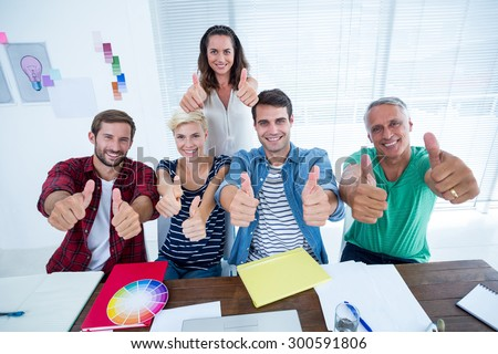 Happy creative business team gesturing thumbs up in meeting at office - stock photo