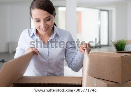 Happy curious woman unpacking and moving into her new office, she is opening a cardboard box and looking into it - stock photo