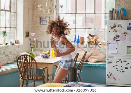 Happy curly haired  girl dancing in kitchen wildly hair bouncing wearing pajamas at home photos on fridge - stock photo