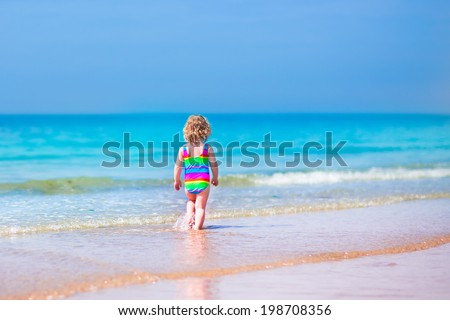 Happy curly little girl in colorful rainbow bathing suit running and playing on ocean coast in water splashes on beautiful tropical island beach with turquoise clear water having fun on vacation - stock photo