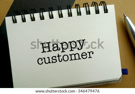 Happy customer memo written on a notebook with pen - stock photo
