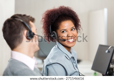 Happy customer service representatives talking with each other in call center - stock photo