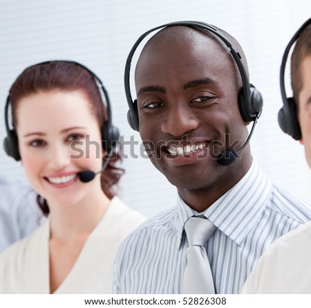 Happy customer service representatives with headset on standing in a line - stock photo
