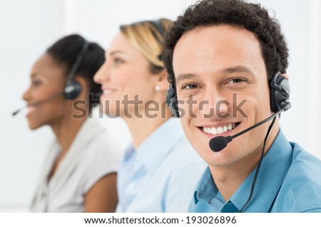 Happy Customer With Headsets Working With Other Colleague In Call Center - stock photo