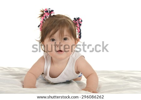 Happy cute baby girl lying on a blanket on a white background