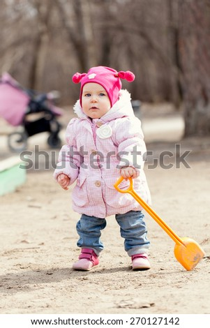 Happy cute baby girl walks in spring park, first steps