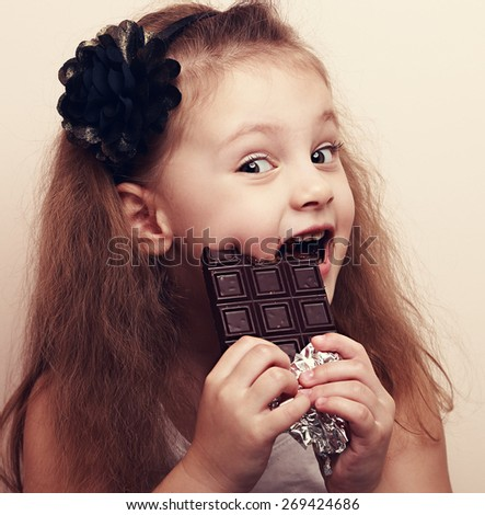 Happy cute beautiful kid girl biting sweet chocolate. Vintage closeup color portrait - stock photo