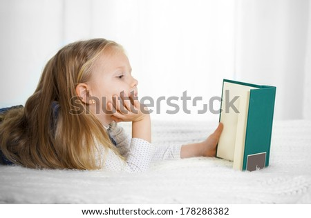 happy cute blonde haired school girl wearing a school uniform reading a book lying on the bed - stock photo