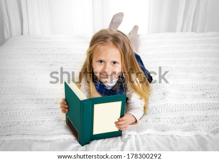 happy cute blonde haired school girl wearing a school uniform reading a book smiling at the camera lying on the bed - stock photo