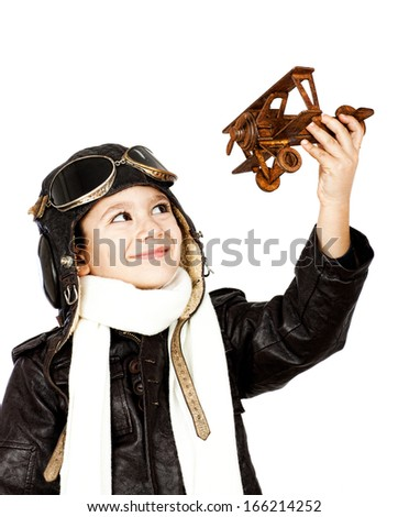 Happy cute boy dressed like a World War II pilot playing with wooden airplane toy isolated on white background.Vintage look