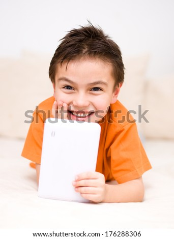 Happy cute boy using tablet computer