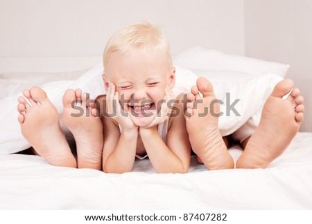 happy cute boy with his mother and father under the blanket in bed at home - stock photo