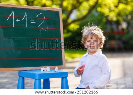 Happy cute child at blackboard practicing mathematics, outdoor school or nursery. - stock photo