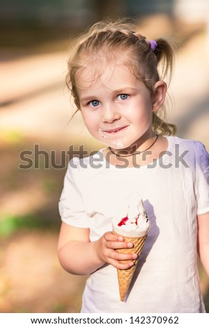 Happy cute child eating ice cream outdoor - stock photo