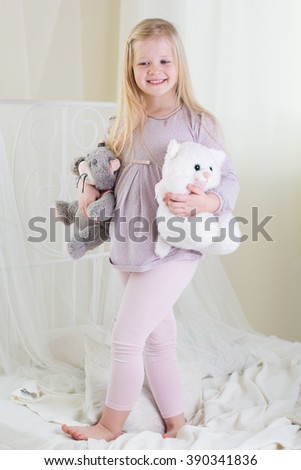 Happy cute child girl standing on the bed - stock photo