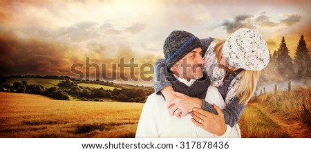 Happy cute couple romancing while embracing each other against country scene - stock photo