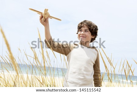 Happy cute elementary boy flying toy airplane among plants on beach - stock photo