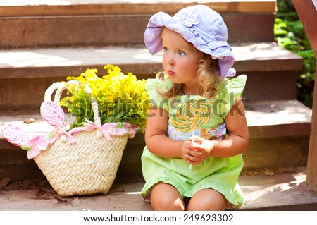 Happy cute european toddler girl in colorful clothes and hat outdoors near wooden stairs with basket of flowers and round candy in hands  - stock photo