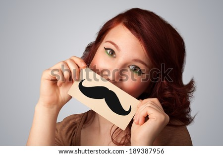 Happy cute girl holding paper with mustache drawing on gradient background