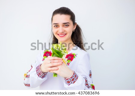 Happy cute girl in the Ukrainian national costume with flowers