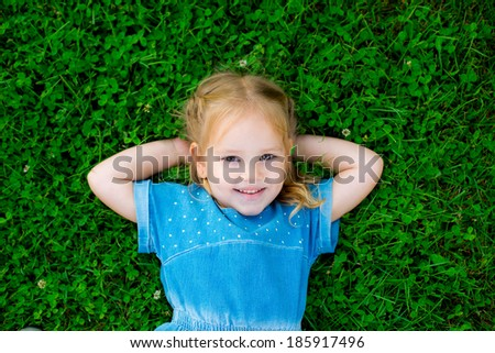 Happy cute girl on green grass in spring park. Healthy lifestyles concept. clover - stock photo
