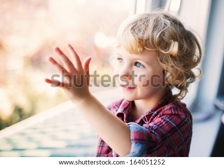 Happy Cute girl sitting alone near window  - stock photo