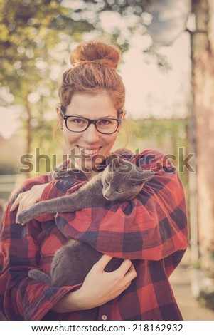 Happy cute hipster girl being silly and playing with her Russian Blue cat - stock photo
