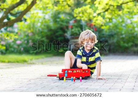 Happy cute kid boy in colorful clothes playing with red wooden bus and toys in summer garden. On warm sunny summer day. Child having fun outdoors. - stock photo