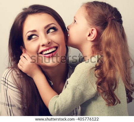 Happy cute kid girl whispering the secret to her smiling mother in ear with fun face. Toned closeup portrait - stock photo