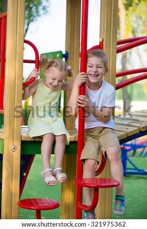 Happy cute kids having fun at playground - stock photo