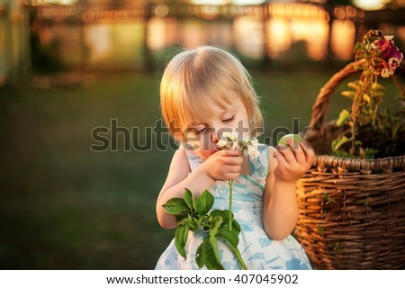 Happy cute little blonde girl two years sitting on the bench under the apple tree next to a basket of flowers and smelling a flower, a sunset of warm summer days, beautiful light - stock photo