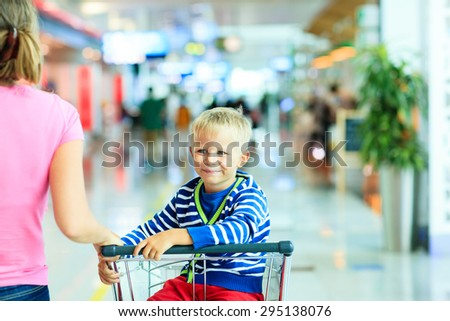 Happy cute little boy at airport riding on luggage cart