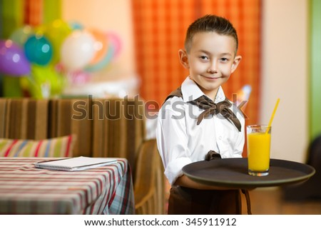 Happy cute little boy smiling waiter holding a tray width juice - stock photo