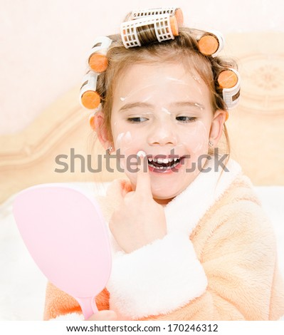 Happy cute little girl in hair curlers with mirror applying cream at home