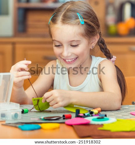 happy cute little girl is engaged in sewing - stock photo