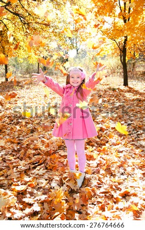 Happy cute little girl playing with maple leaves in the autumn park  - stock photo