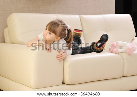 happy cute little girl relax  on sofa at home - stock photo