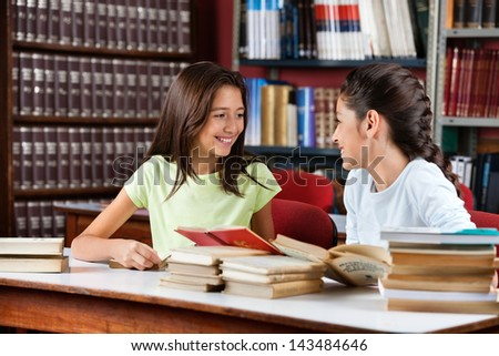 Happy cute little schoolgirls looking at each other while studying at table in library - stock photo
