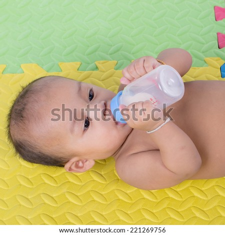 Happy cute 5 month old Asian baby boy with drinking milk on rubber floor - stock photo