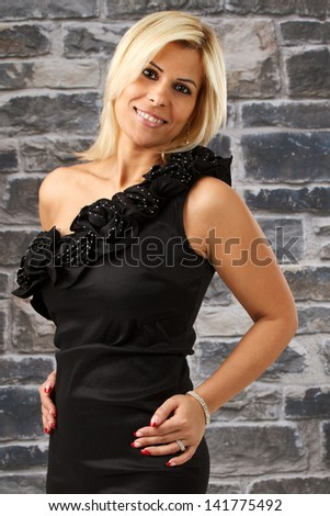 Happy cute party girl in front of brick wall