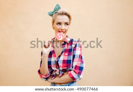 Happy cute pin up girl standing and eating colorful lollipop over pink background