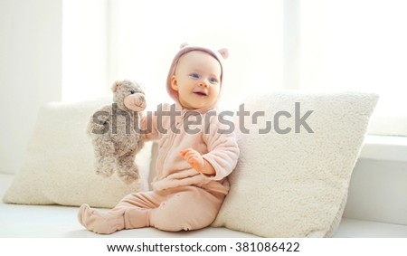 Happy cute smiling baby with teddy bear toy at home in white room near window - stock photo