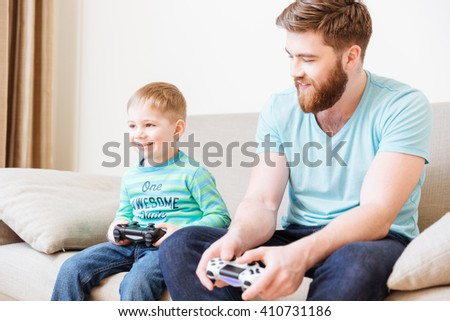 Happy cute son sitting on couch and playing computer games  with his father at home - stock photo