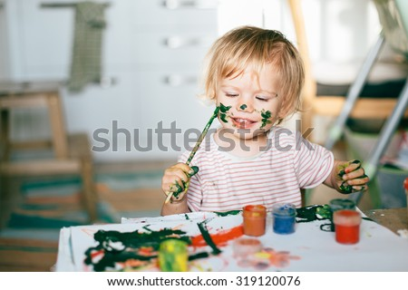 Happy cute toddler painting her face with gouache paints - stock photo