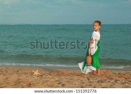 Happy cute young girl in the emerald dress in antique style keeps the old amphora on the sea coast/Beautiful Greek goddess