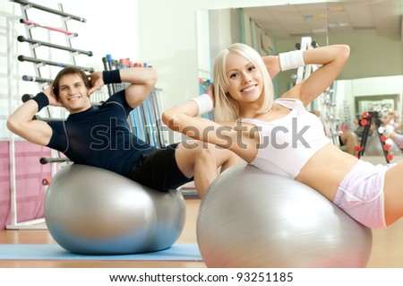 happy cutie athletic girl and guy,  execute exercise on muscles belly  on balls and smile, in  sport-hall - stock photo