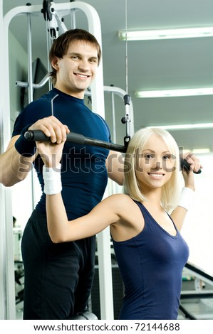happy cutie athletic girl and guy,  execute exercise on sport-apparatus  and smile, in  sport-hall