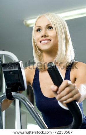 happy cutie athletic girl ,  execute exercise on exercise bicycle  and smile, in  sport-hall, close face