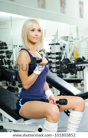 happy cutie athletic girl ,  exercise with dumbbells and smile, in  sport-hall