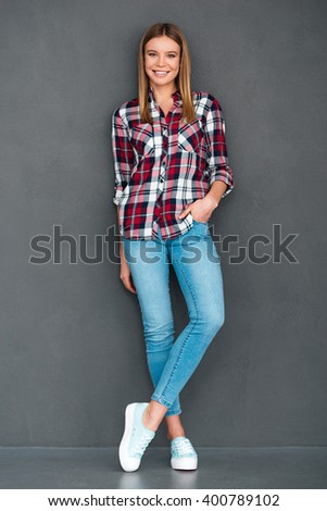 Happy cutie. Full length of beautiful young woman keeping hand in pocket and looking at camera with smile while standing against grey background - stock photo